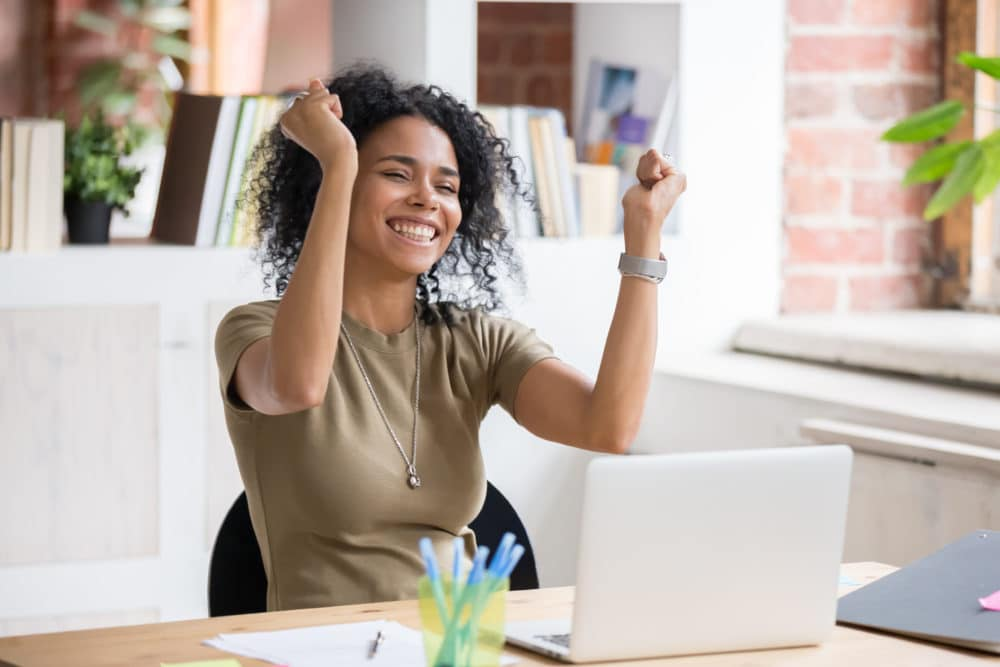 A girl celebrating at her computer.